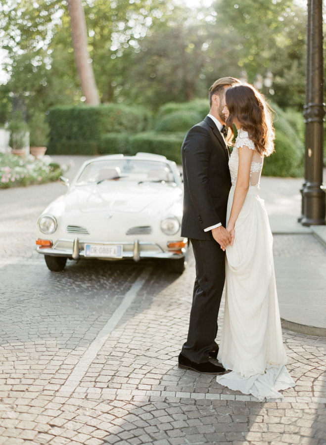 Bride and groom kissing before making their exit in a luxury sport car