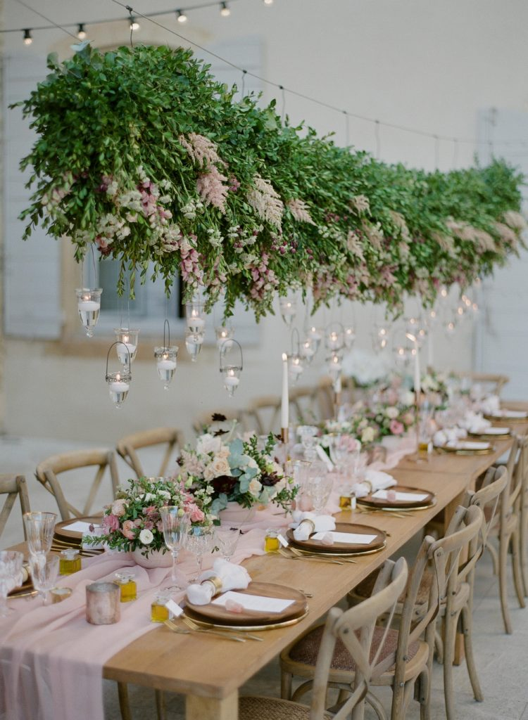 Wedding reception table decor with a suspended floral installation and hanging candles