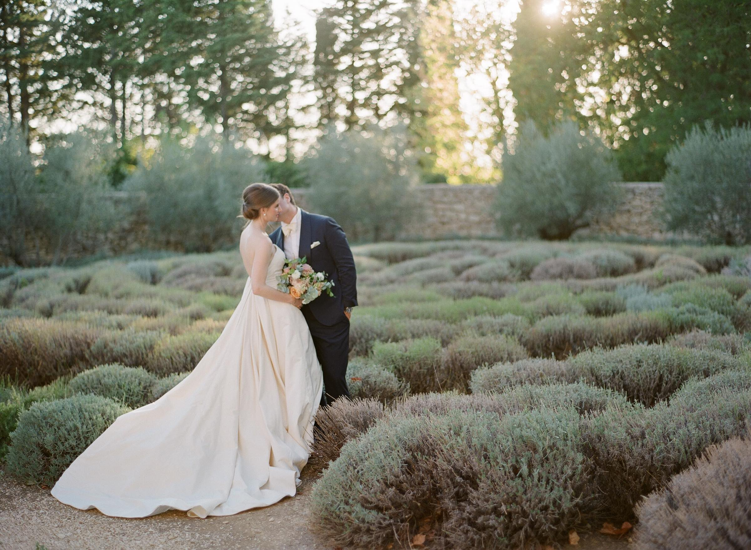 Groom kissing his bride in a lavender garden