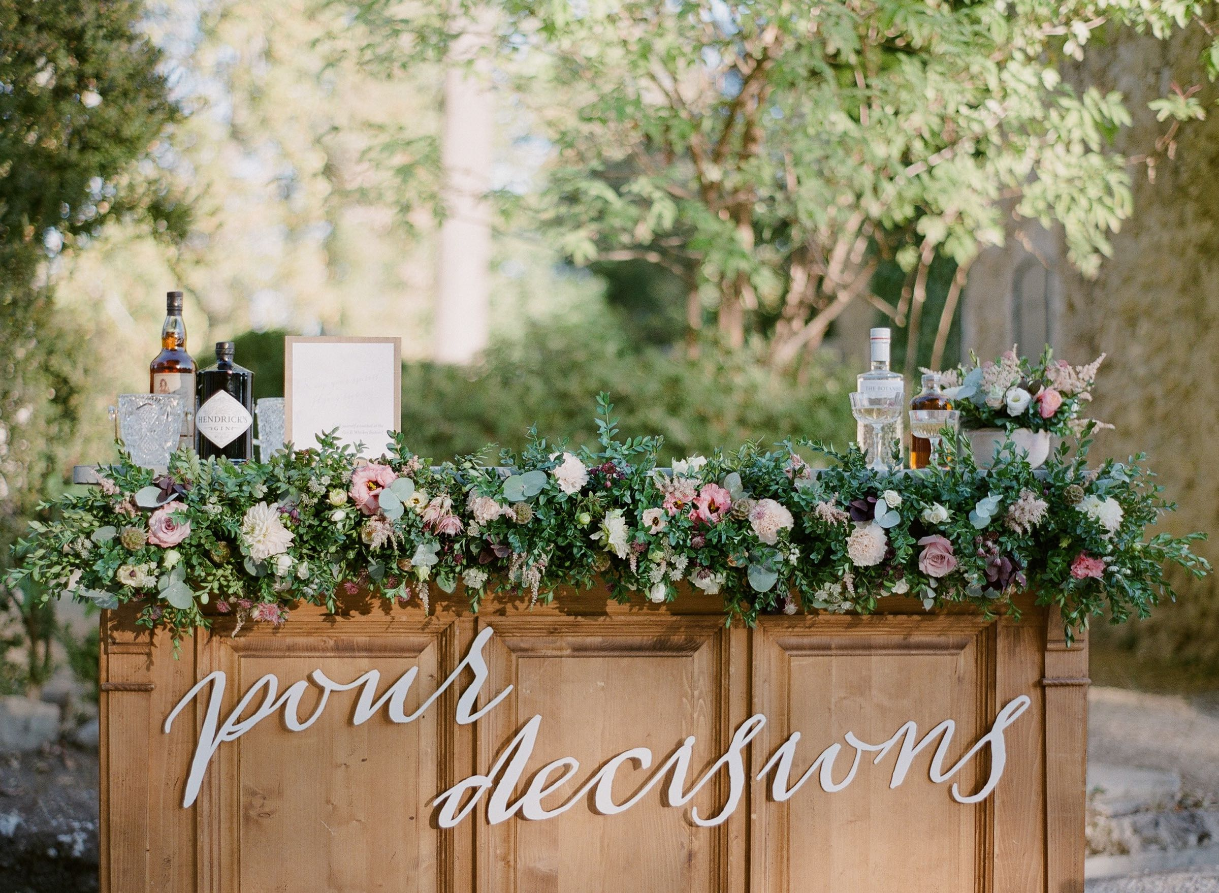 Wedding bar adorned with lush floral decor and laser-cut lettering