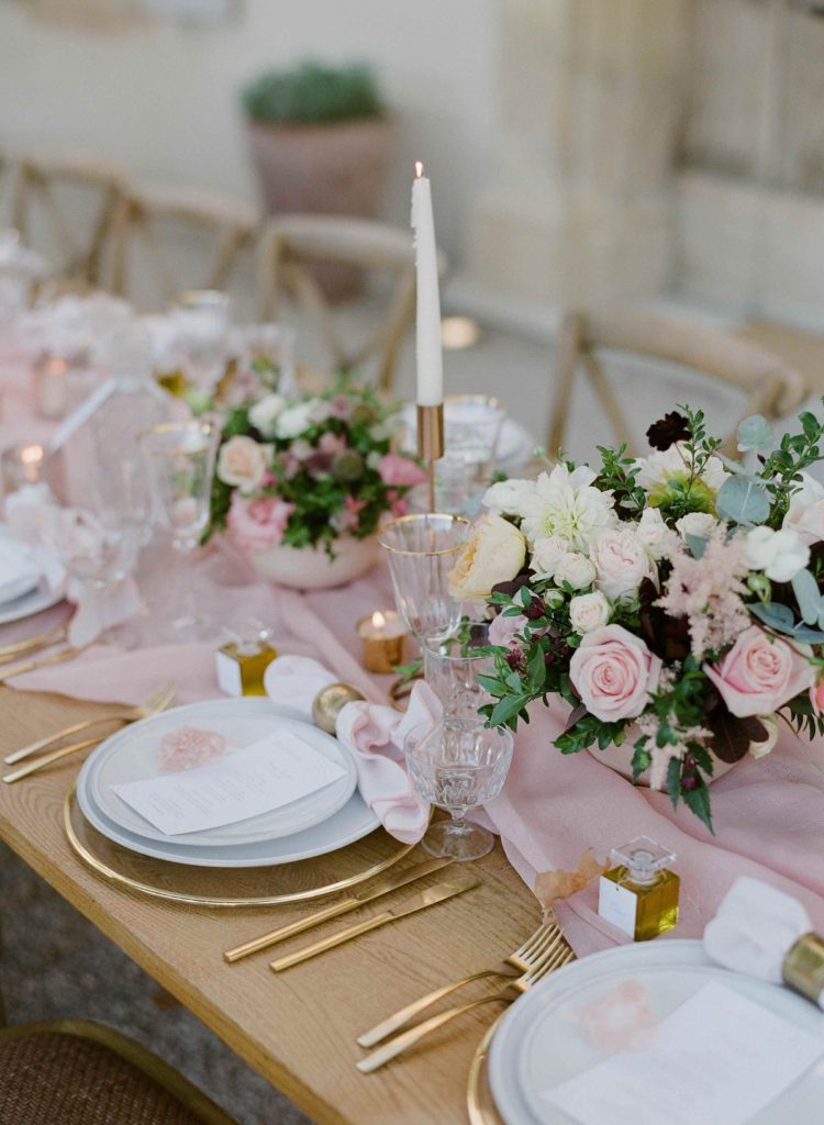 Wedding table decor with mauve silk runners and golden accents