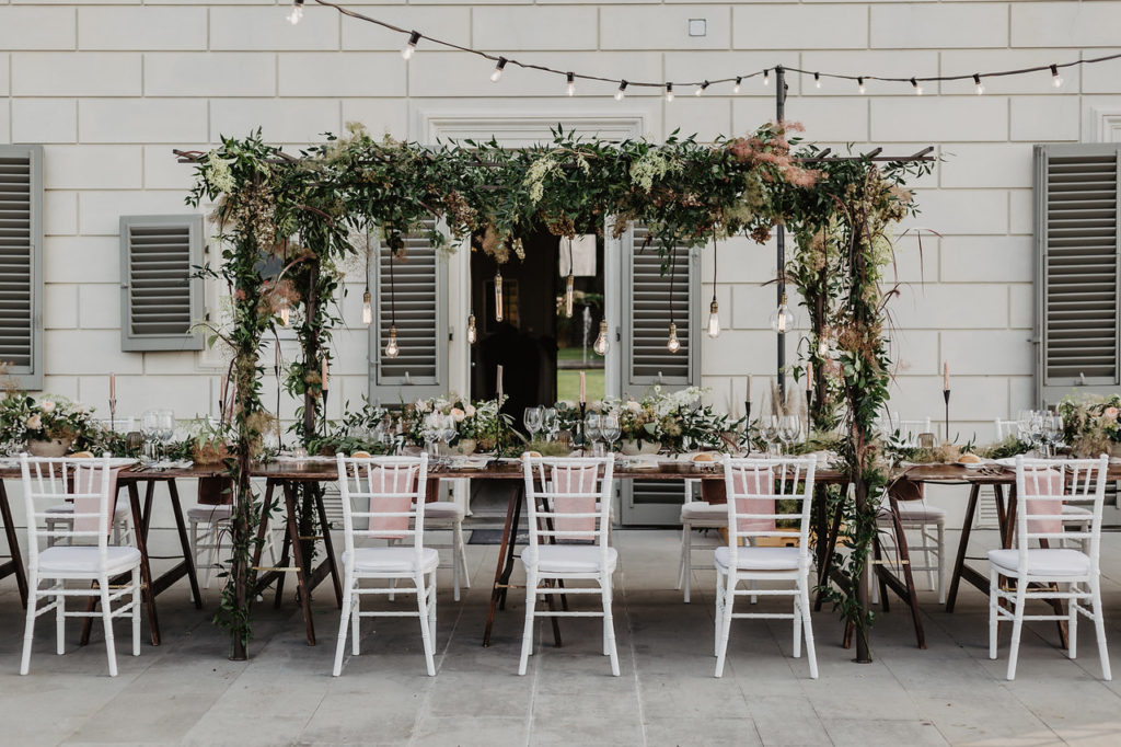Wedding table decor with canopy floral installation and hanging retro light bulbs