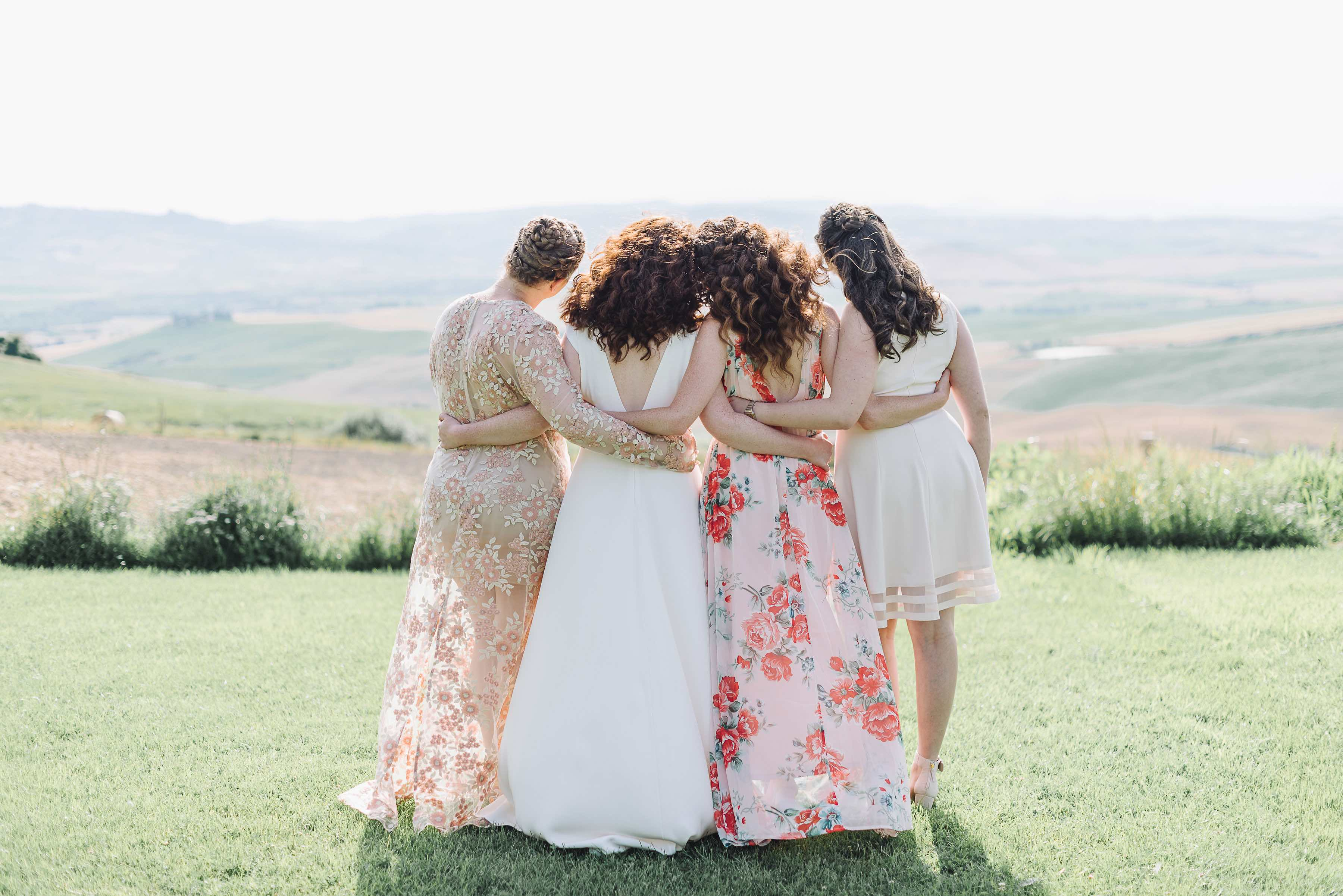 The bride and her bridesmaids arm in arm