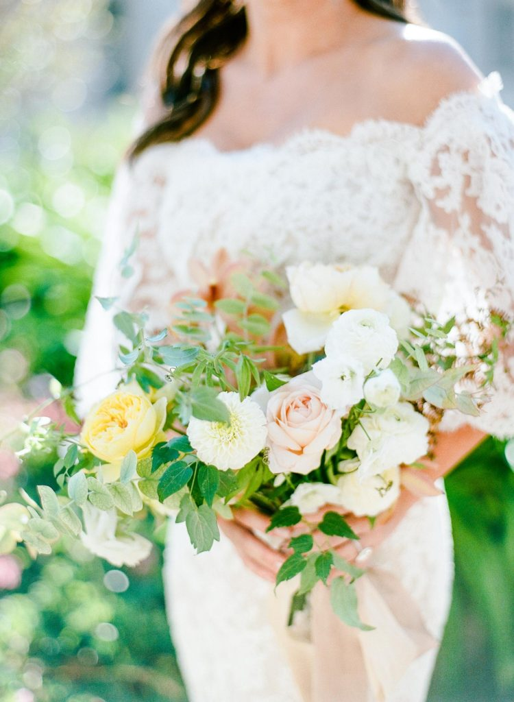 Bride in a lace gown holding a romantic bouquet