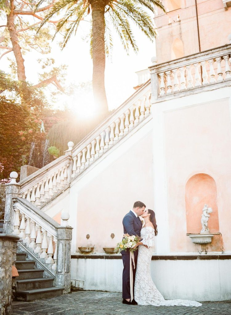 Bride and groom kissing at the foot of Palazzo Avino's magical stairs