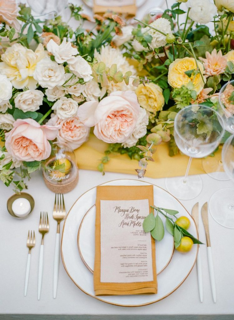 Vibrant wedding table setting in tones of pink, yellow, orange and teal