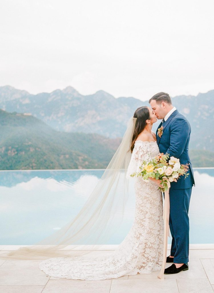 Bride and groom kissing on the backdrop of Hotel Belmond's infinity pool and the mountains